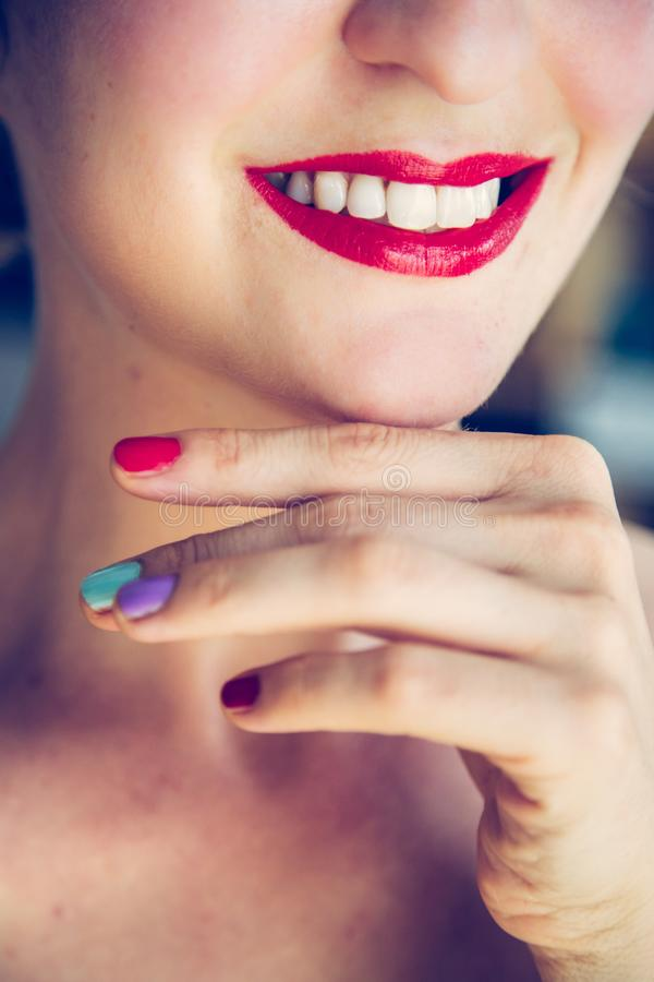 Attractive red lip stick and healthy white teeth: Blonde young woman with colorful nail polish is looking herself in the mirror stock photography