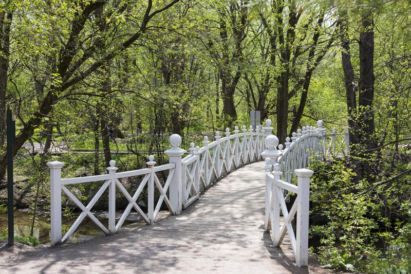 Pretty white wooden pedestrian bridge over stream in Domaine Maizerets public park during sunny spring afternoo stock photography