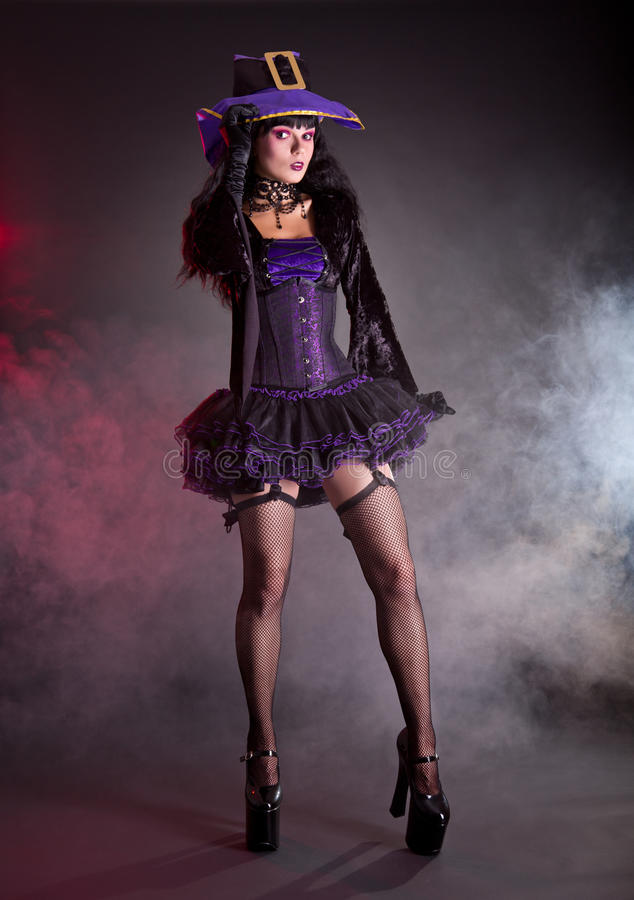 Pretty witch in purple and black gothic Halloween costume. Pretty witch in purple and black gothic fantasy Halloween costume, full length shot royalty free stock photos