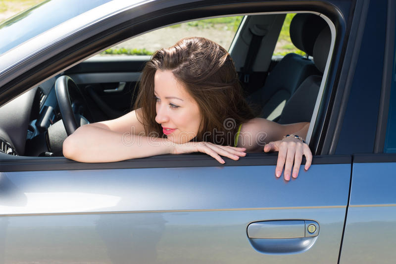 Pretty woman admires a model of her car. stock images