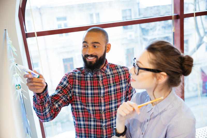 Pretty woman and african man preparing for presentation near whiteboard stock photo