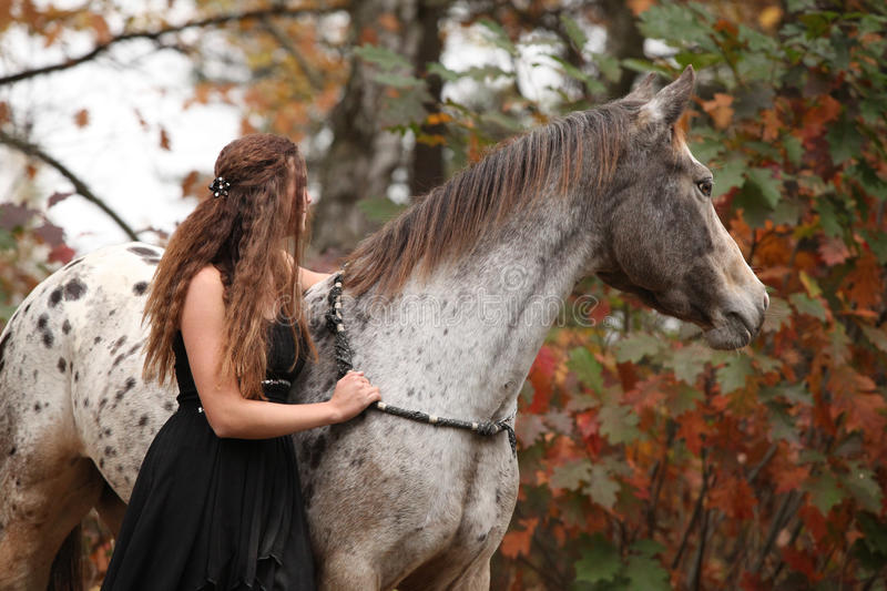 Pretty woman with appaloosa horse in autumn royalty free stock photo
