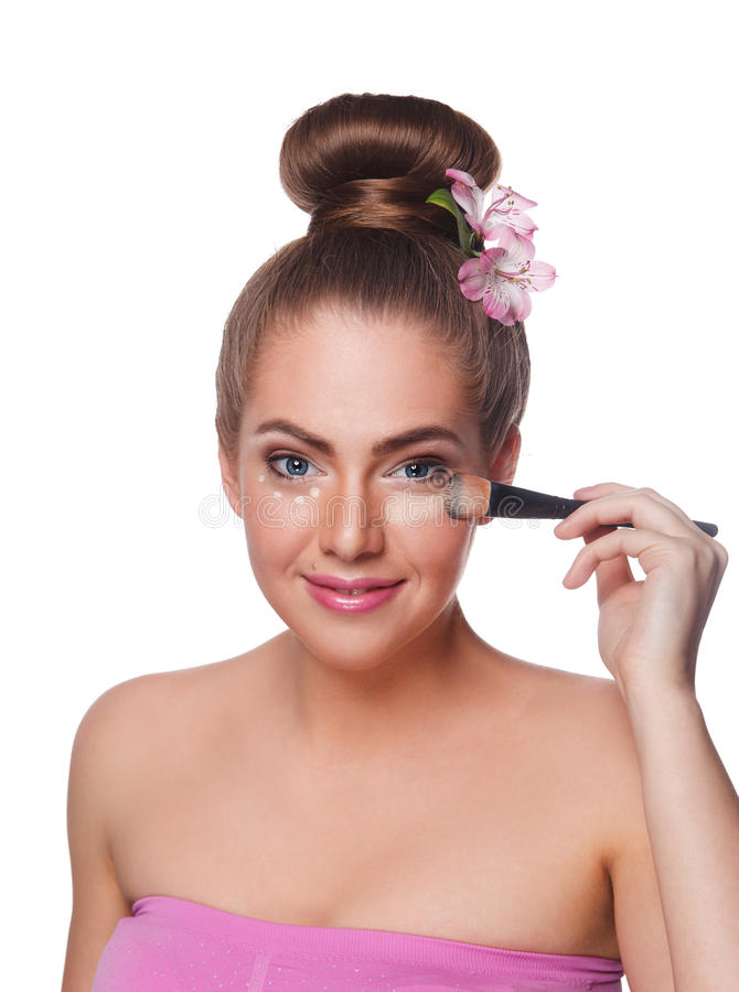 Pretty woman applying concealer with brush. Beautiful young woman applying concealer with makeup brush isolated on white stock images