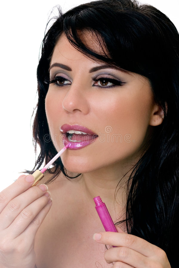 Pretty woman applying lip gloss to lps royalty free stock image