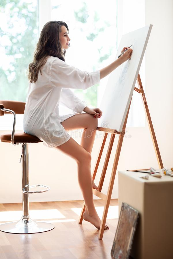 Pretty woman artist painting on canvas in workshop. Pretty woman artist painting on canvas in her workshop royalty free stock image