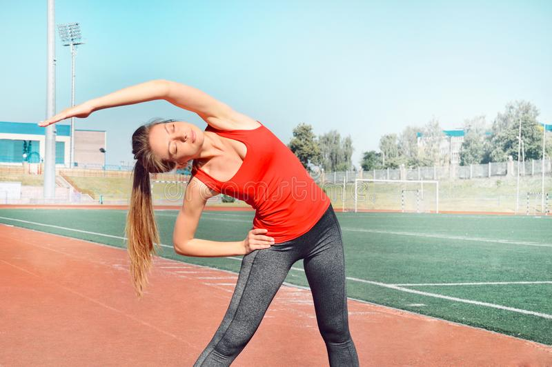 A pretty woman athlete stretching her body at stadium track royalty free stock image