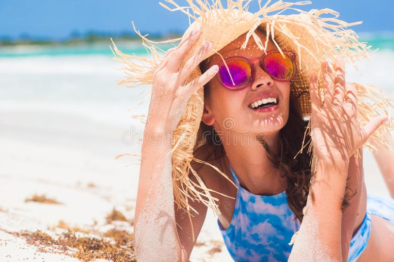 Pretty woman on the beach, closeup portrait of a nice female hides her face from the sun under a straw hat, skin royalty free stock images