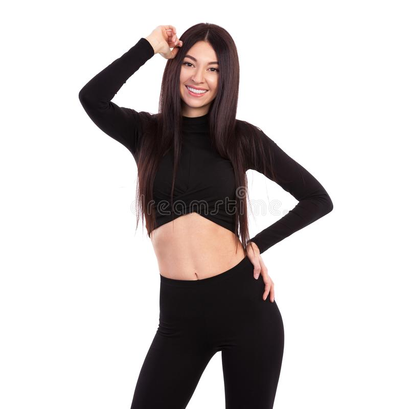 Pretty woman with beautiful long hair in black suit isolated on white background. Close up of sporty and beautiful female body. royalty free stock photography