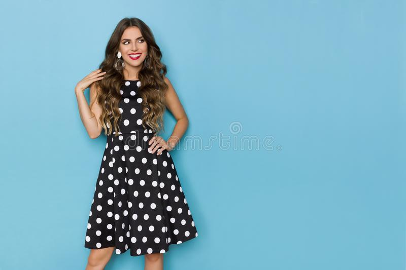 Pretty Woman In Black Coctail Dress In White Dots Is Looking Away And Smiling royalty free stock photo