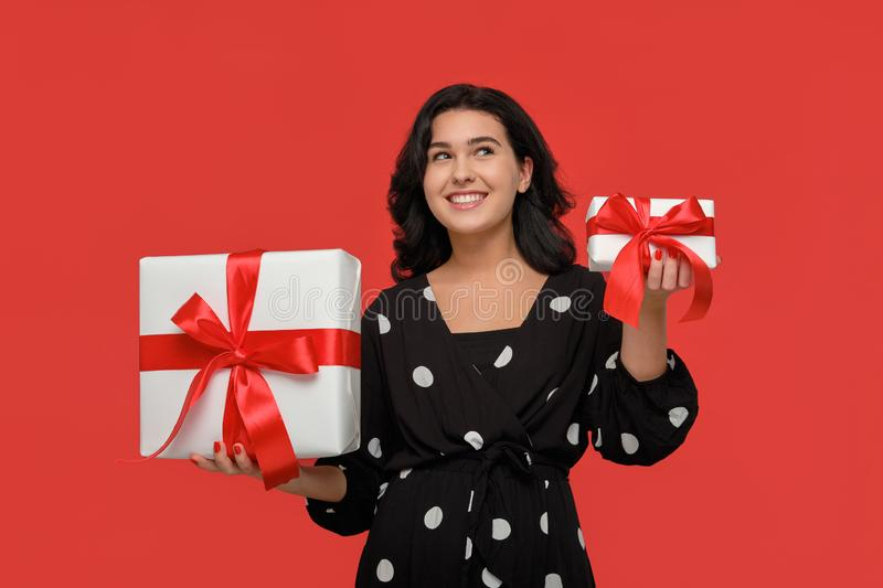 Pretty woman in a black dress choosing between small and big Christmas giftboxes with red ribbon royalty free stock photos