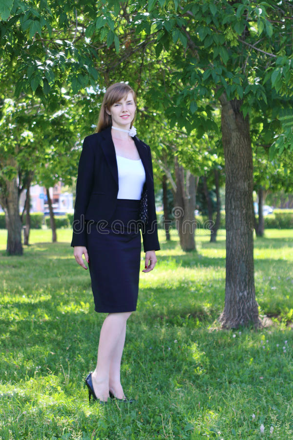 Pretty woman in black suit stands in sunny green park at s. Pretty young woman in black suit stands in sunny green park at summer stock images