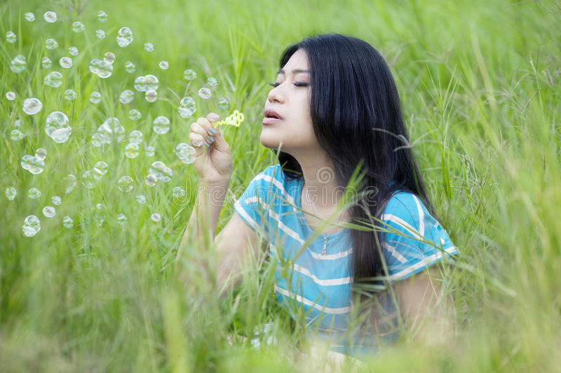 Pretty woman blowing bubble on the meadow stock photography