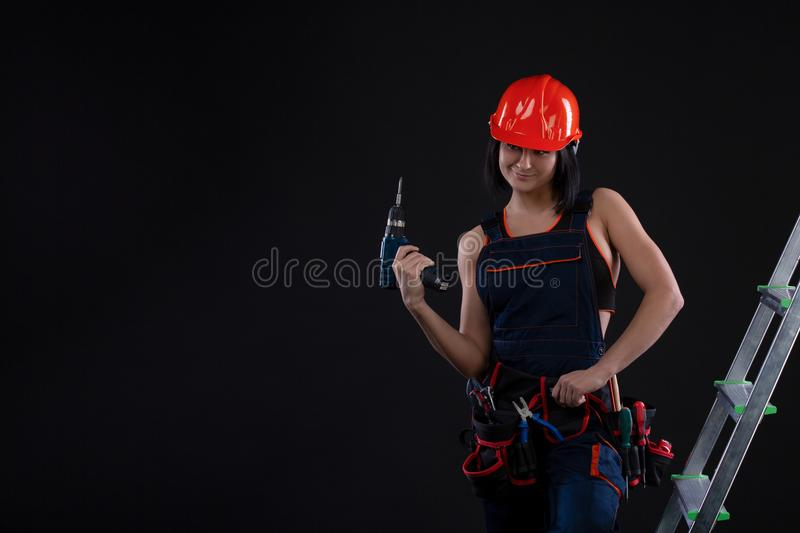 Pretty woman builder in helmet with drill in her hands standing on a ladder and looking away on black background stock image