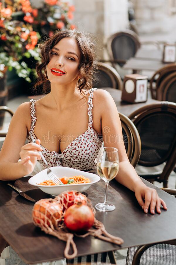 Pretty woman with candid smile laughing sitting at summer cafe, dressed in white printed dress, fashionable street style royalty free stock photo
