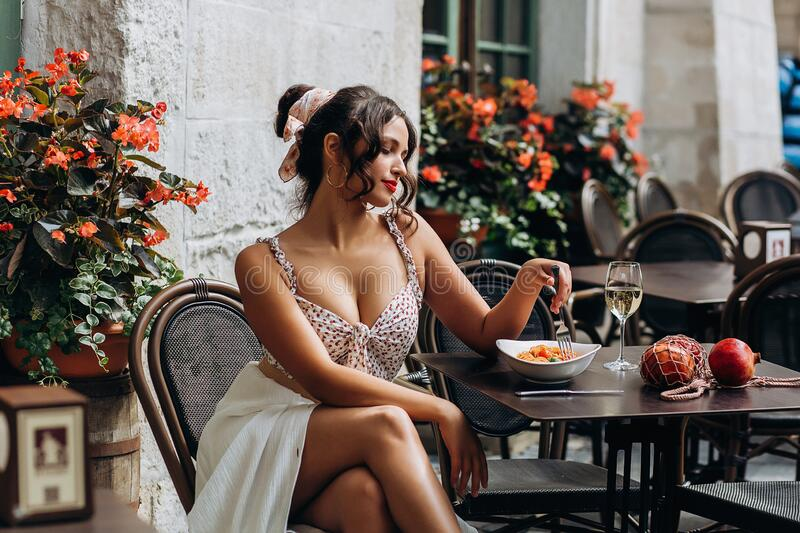 Pretty woman with candid smile laughing sitting at summer cafe, dressed in white printed dress, fashionable street style royalty free stock photos