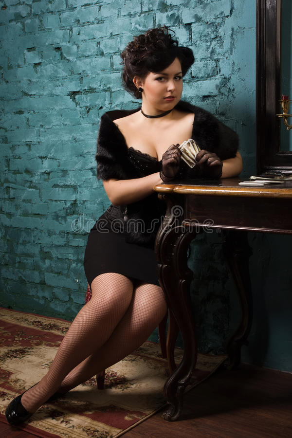 Pretty woman with cards in the vintage interior royalty free stock photography
