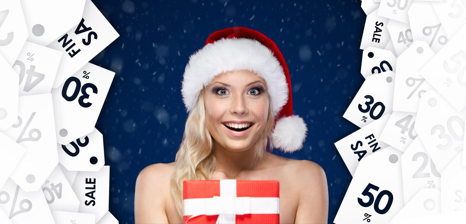 Pretty woman in Christmas cap hands item at a great price stock photo
