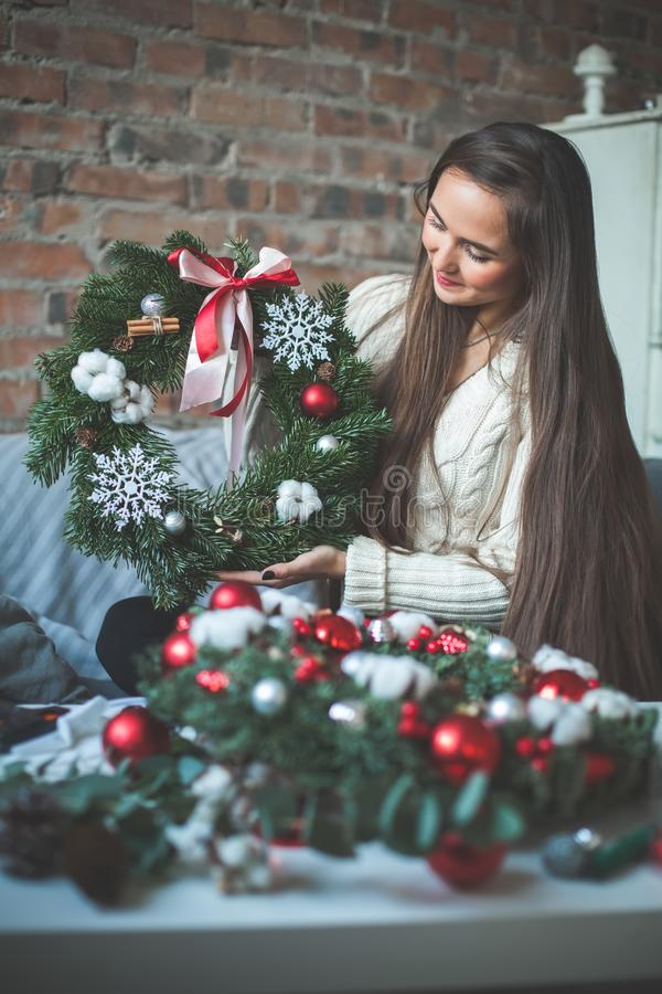 Pretty Woman with Christmas Tree Wreath at Home. Real People Portrait stock photo