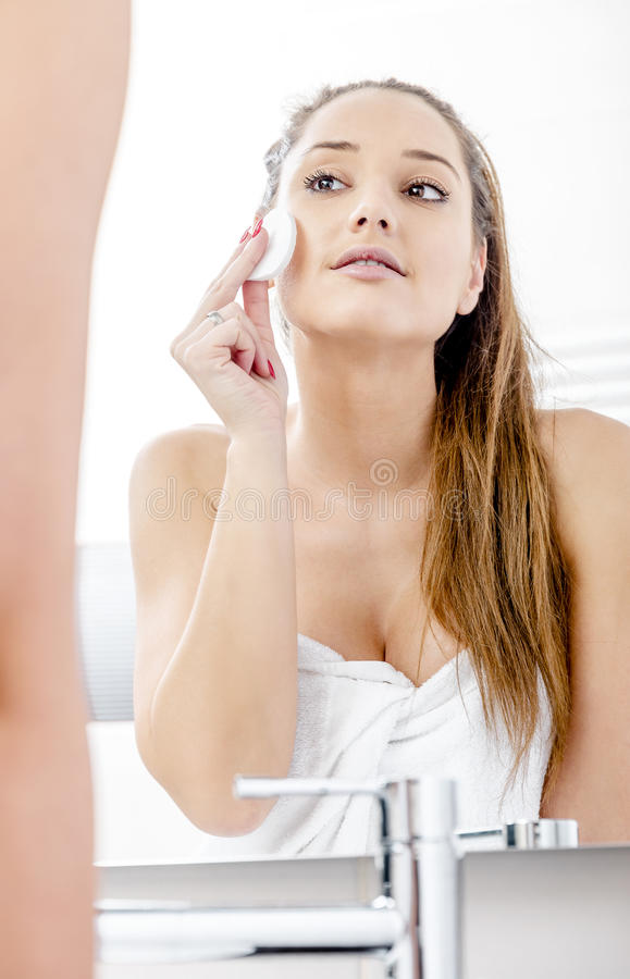Pretty woman cleaning her face stock photos