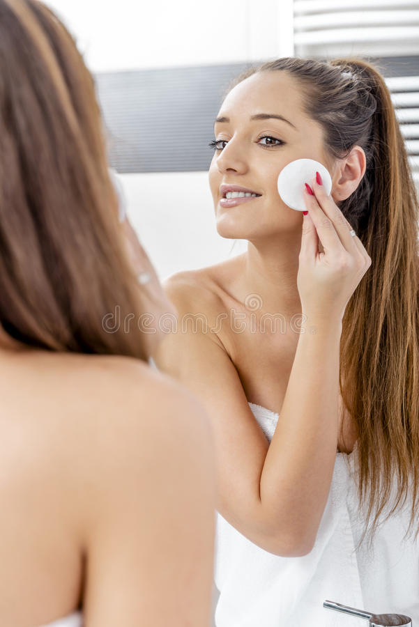 Pretty woman cleaning her face stock image