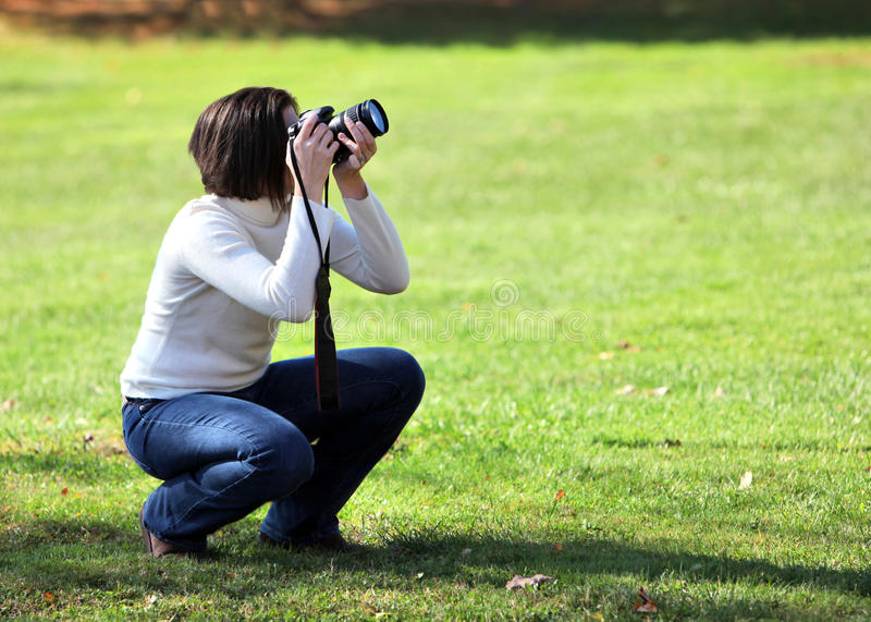 Pretty woman crouching with camera. Outdoors stock photo