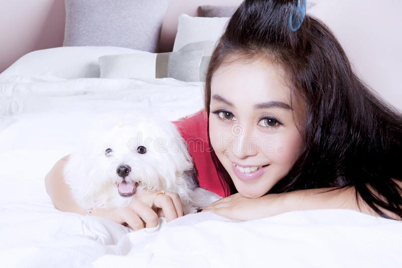 Pretty woman with cute dog on bed stock image