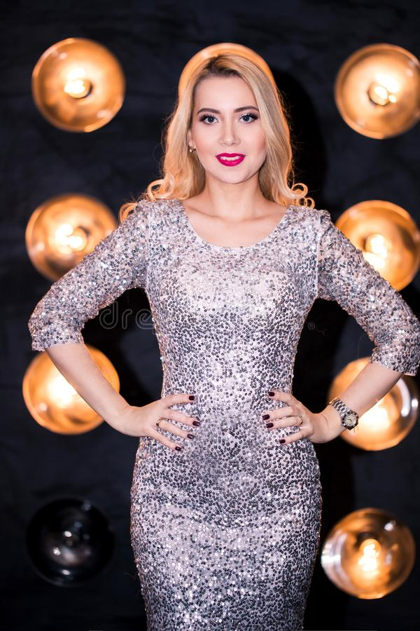 Pretty woman or cute girl in silver sequins dress and trendy makeup on face. party and holiday. Celebration royalty free stock images
