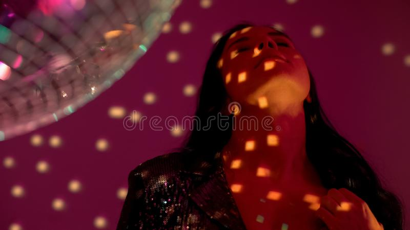 Pretty woman dancing by disco ball at party in night club, escape from stress. Stock photo stock photos