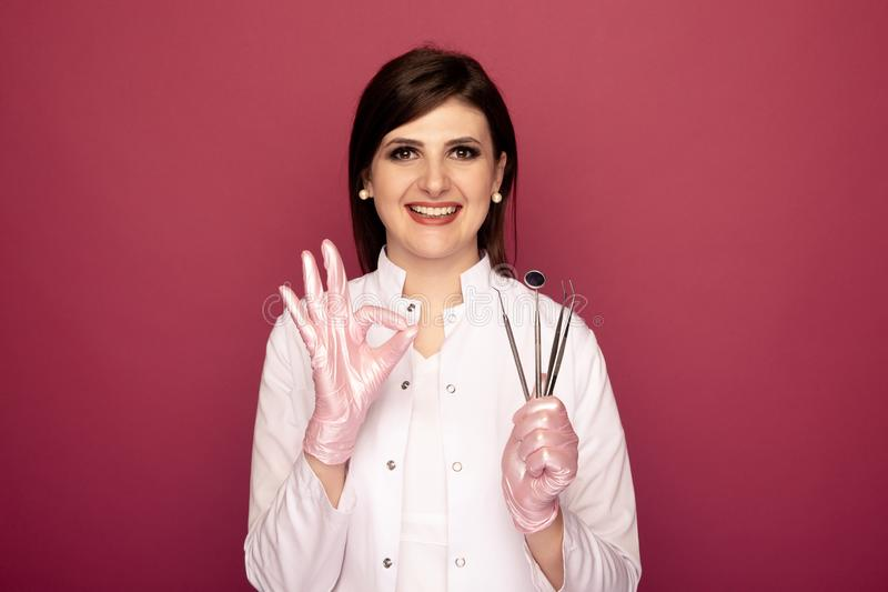 Pretty woman dentist with dental stuff in the dark pink studio. royalty free stock photography
