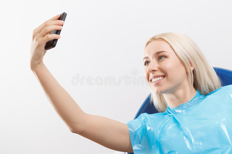 Pretty woman doing selfie at dentist. Selfie time. Pretty youthful smiling blond-haired woman sitting in armchair at office of dentist and doing selfie royalty free stock photos