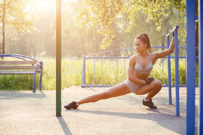 Pretty woman doing sport stretching exercises in the summer outdoor. royalty free stock photos