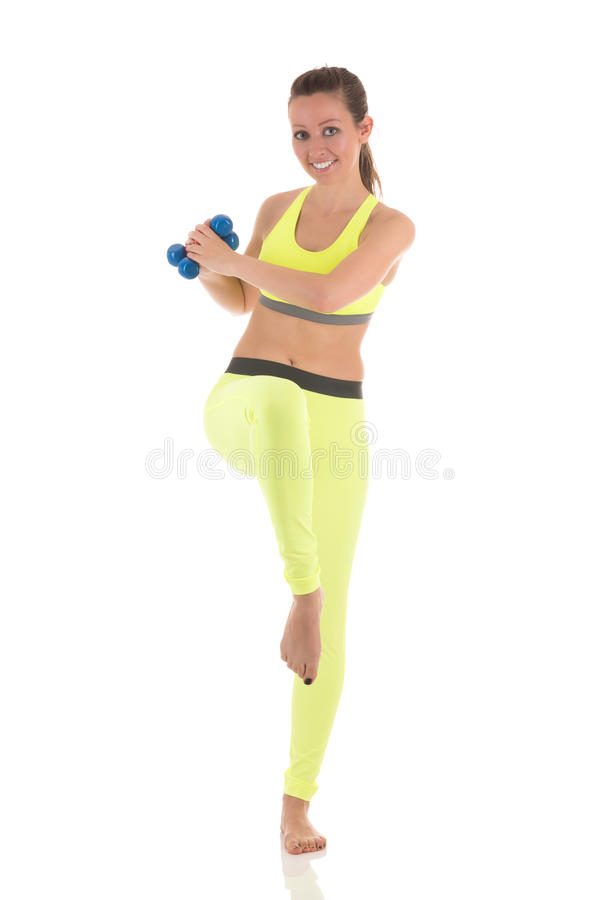 Pretty woman doing wearing sports neon yellow bra and leggings doing exercises for press muscles in a standing position using two stock photos
