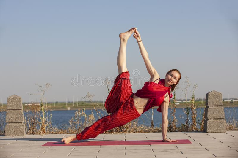 Pretty woman doing yoga exercises in the park. Portrait stock photo