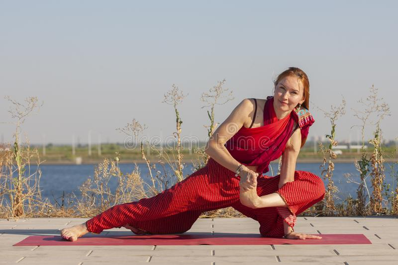 Pretty woman doing yoga exercises in the park. Portrait royalty free stock images