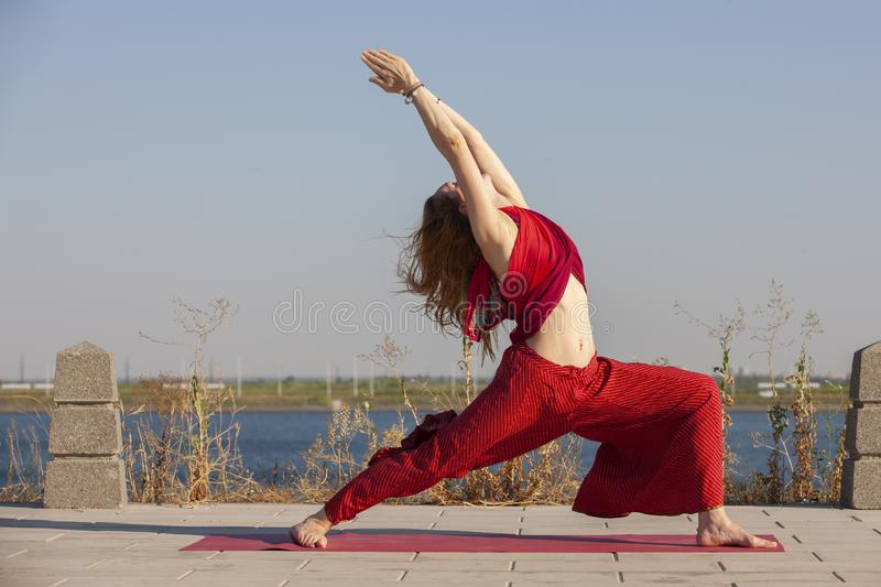 Pretty woman doing yoga exercises in the park. Portrait royalty free stock image