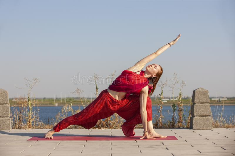 Pretty woman doing yoga exercises in the park. Portrait stock photography