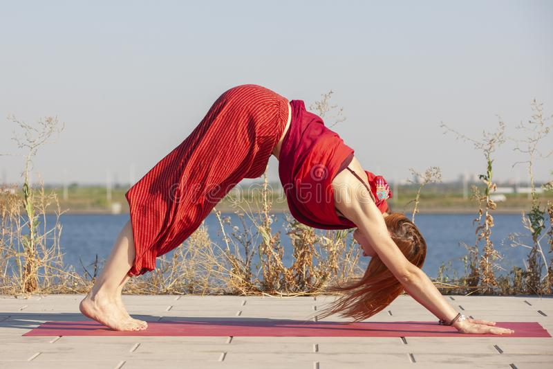 Pretty woman doing yoga exercises in the park. Portrait stock photos