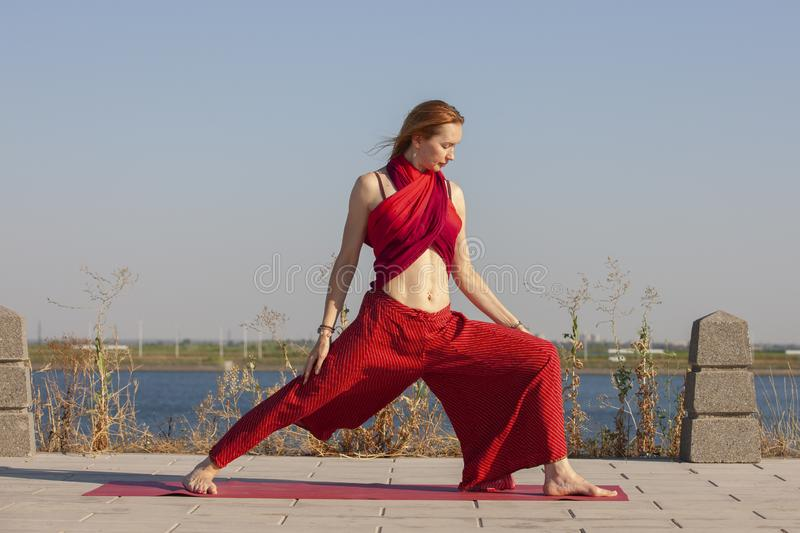 Pretty woman doing yoga exercises in the park. Portrait royalty free stock photography
