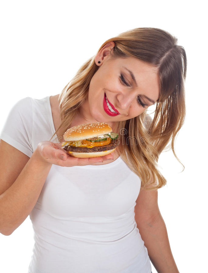 Pretty woman eating a delicious hamburger. Picture of a pretty young woman eating a delicious hamburger, posing on isolated background stock photo
