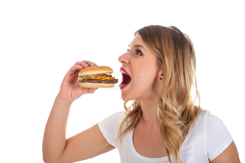 Pretty woman eating a delicious hamburger. Picture of a pretty young woman eating a delicious hamburger, posing on isolated background royalty free stock photo