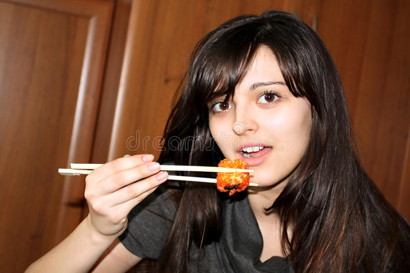 Pretty woman eating sushi royalty free stock photo