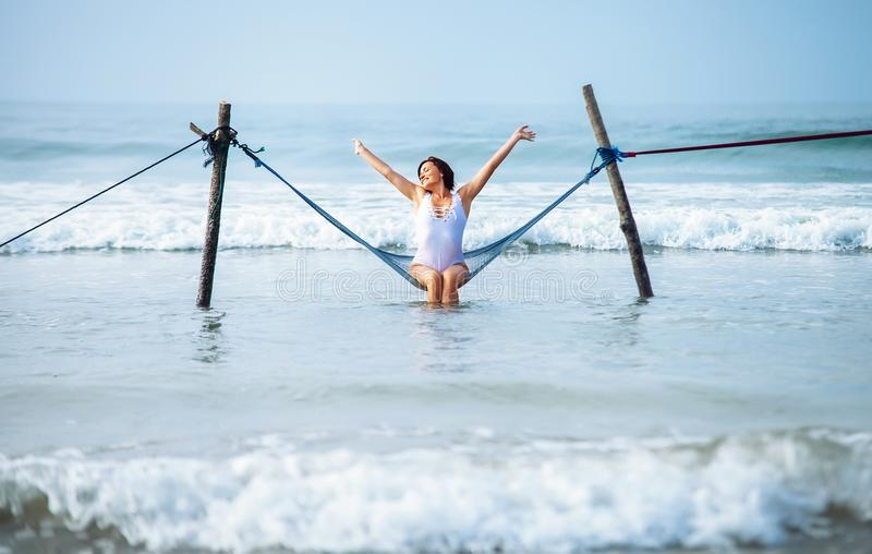 Pretty woman enjoy with ocean breeze and sun sits in hammock swing over the waves stock photography