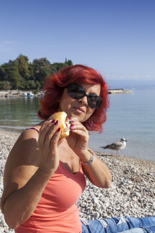 Free Pretty Woman Enjoying Fresh Sea Food Sandwich Stock Image - 45642901