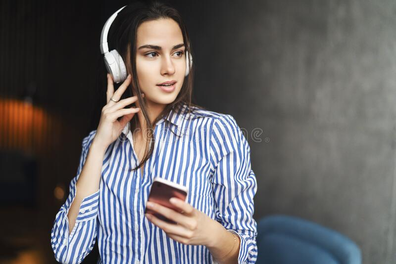 Pretty woman enjoying great sound of music in wireless headphones. Girl listening to audio content and streaming songs online in. Pretty young woman enjoying royalty free stock photography