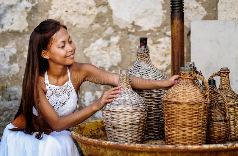 Pretty woman in ethnic Mediterranean folk traditional costume holding a rattan olive oil jug. Hospitality and ethnic tourism conce. Pt stock images