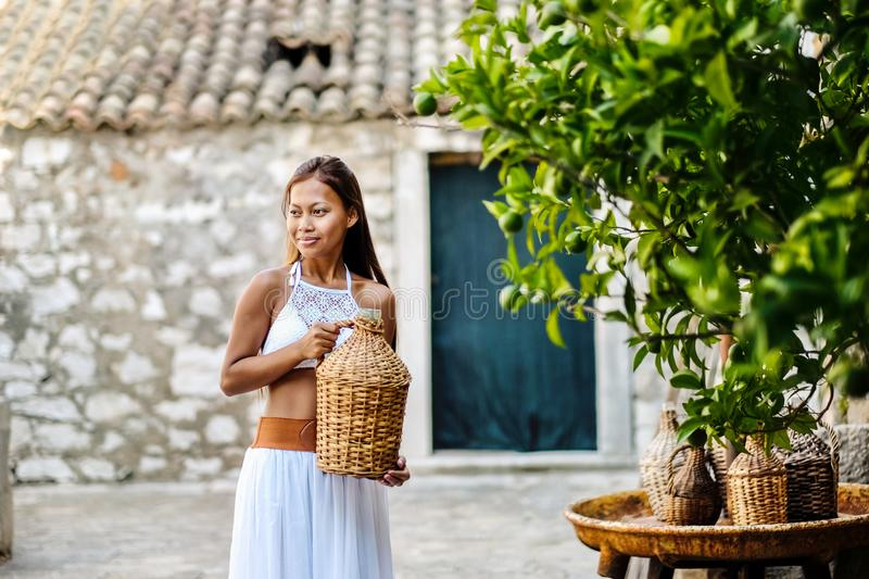 Pretty woman in ethnic Mediterranean folk traditional costume holding a rattan olive oil jug. Hospitality and ethnic tourism conce. Pt royalty free stock photo