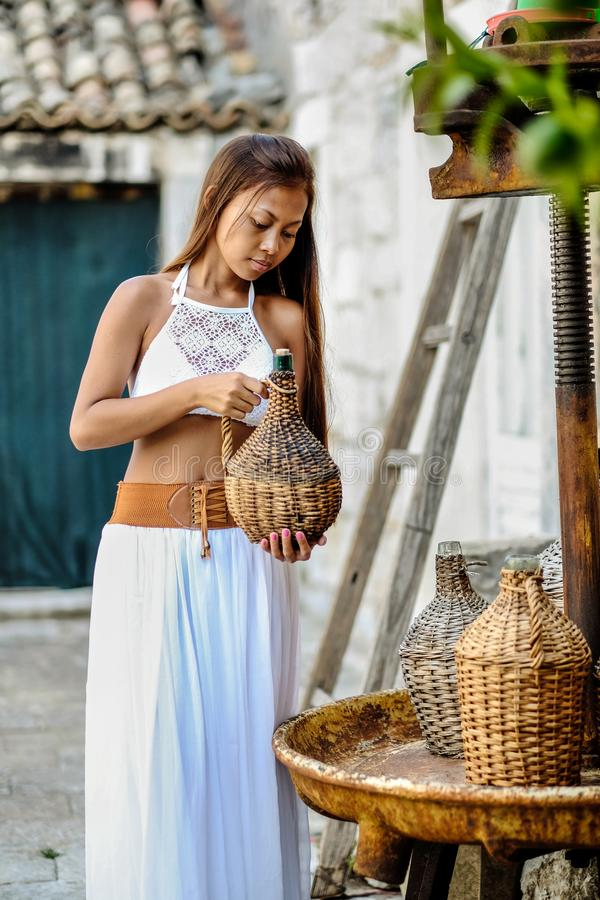 Pretty woman in ethnic Mediterranean folk traditional costume holding a rattan olive oil jug. Hospitality and ethnic tourism conce. Pt stock photo