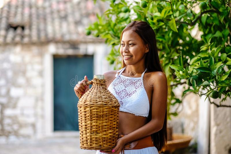 Pretty woman in ethnic Mediterranean folk traditional costume holding a rattan olive oil jug. Hospitality and ethnic tourism conce. Pt stock photos