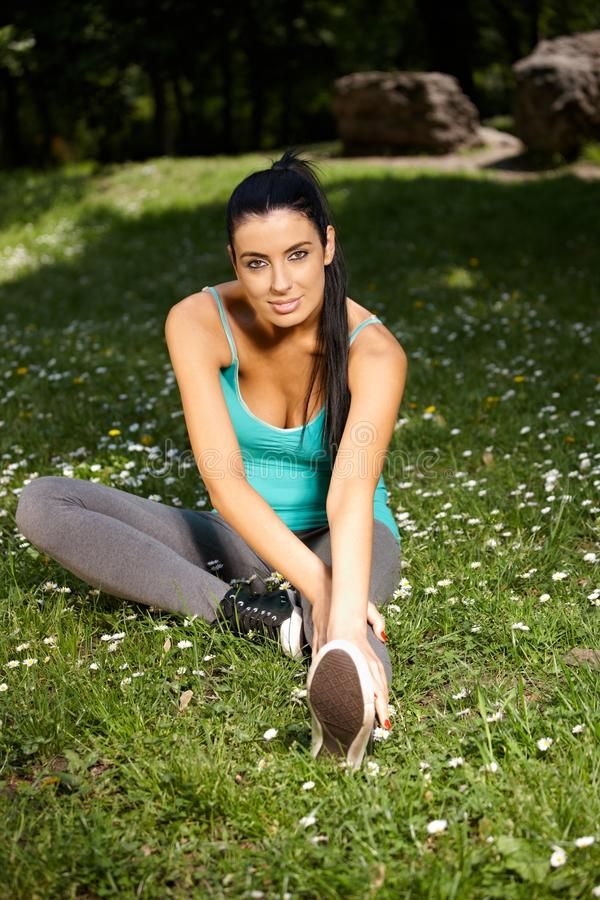 Pretty woman exercising in citypark smiling royalty free stock image