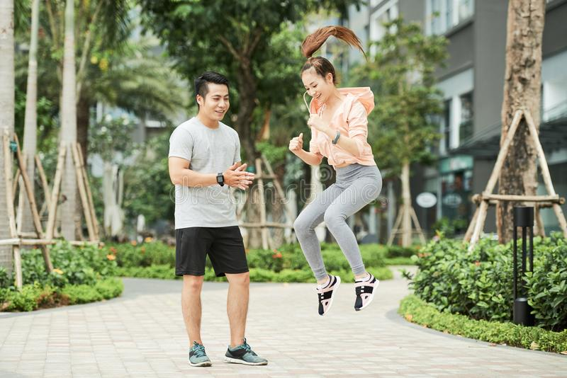Pretty woman exercising with trainer royalty free stock images
